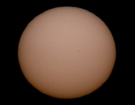 Zwakkelre Zon en wazig planeetschijfje kort voor zonsondergang.  Meer oranje kleur.